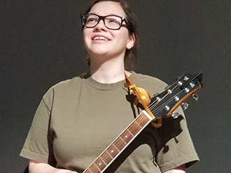 Student holding a guitar