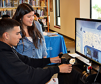 Fontana Unified students practice piloting a Cessna 172 on a flight simulator, gaining insight into
